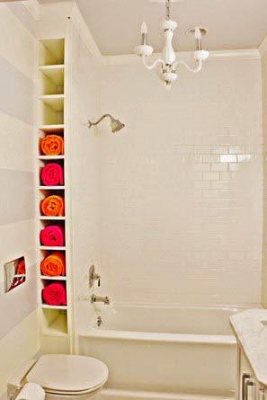 Une étagère le long de la baignoire pour ranger les serviettes de bains